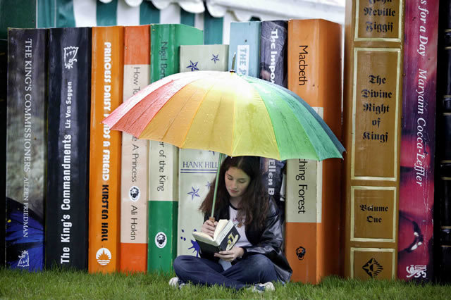 A girl absorbed in a book despite the rain at the Hay-on-Wye Book Festival