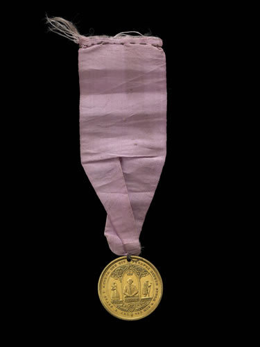 Commemorative medal: Royal Dramatic College; gilt-metal; pierced for suspension; pink ribbon attached; obverse: view of long building; legend; reverse: three Gothic arches; Shakespeare crowned; woman carrying child; aged man; foliate scrolls, © The Trustees of the British Museum