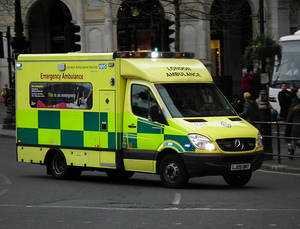 An ambulance drives with flashing blue lights