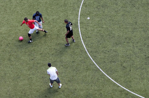 Footballers play on a pitch in Camden