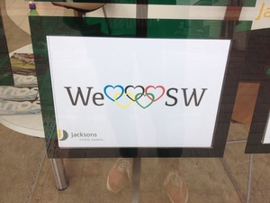 A sign in estate agent window showing olympic rings as hearts