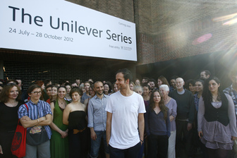 ****FREE USAGE**** Artist Tino Sehgal is photographed with his participants outside Tate Modern in London, two days prior to the unveiling of his commission in the annual Unilever Series for Tate Modern's Turbine Hall. Photo date: Sunday July 22, 2012. The work, which will feature his participants and their encounters with visitors, will be unveiled on July 24 and will be the thirteenth to be commissioned in The Unilever Series. Sehgal has risen to prominence for his innovative works which consist purely of live encounters between people. Avoiding the production of any objects, he has pioneered a radical and yet entirely viewer-oriented approach to making art. His works respond to and engage with the gallery visitor directly, creating social situations through the use of conversation, dance, sound and movement, as well as philosophical and economic debate. Having trained in both political economics and choreography, the resulting works are renowned for their high levels of interaction, intimacy, and critical reflection on their environment. The Unilever Series is an annual art commission sponsored by Unilever. Photo credit: Johnny Green