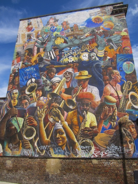 The Hackney Peace Carnival mural in Dalston. It was designed by Ray Walker in 1984, but he died before realising it. The wall was instead painted by his wife and Mick Jones.
