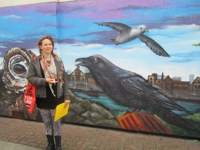 Ruth Miller in front of the Tawny Way mural near Surrey Quays, showing birds whose names can be found on the surrounding estate. The mural was created by Positive Arts in 2012.