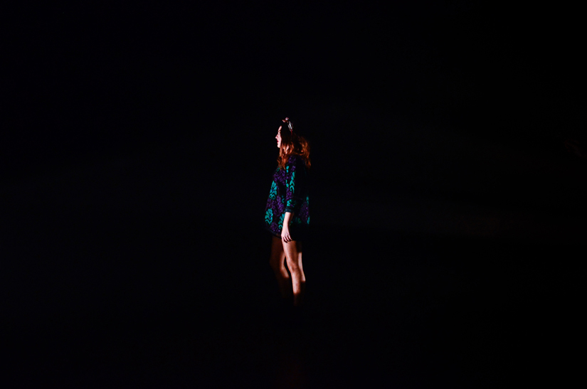 A woman steps into the light of an art installation at The Tate Tanks, July 2012