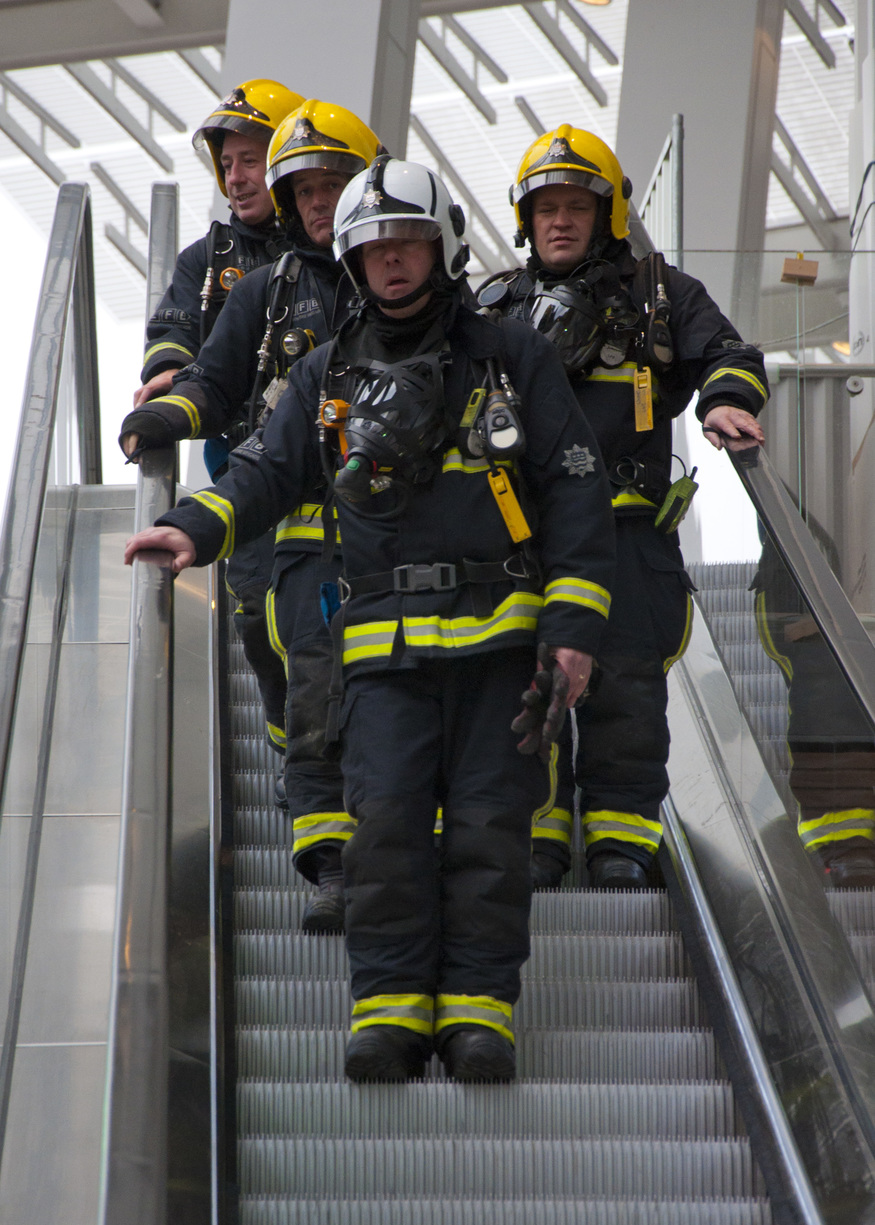 Firefighters travel down an escalator