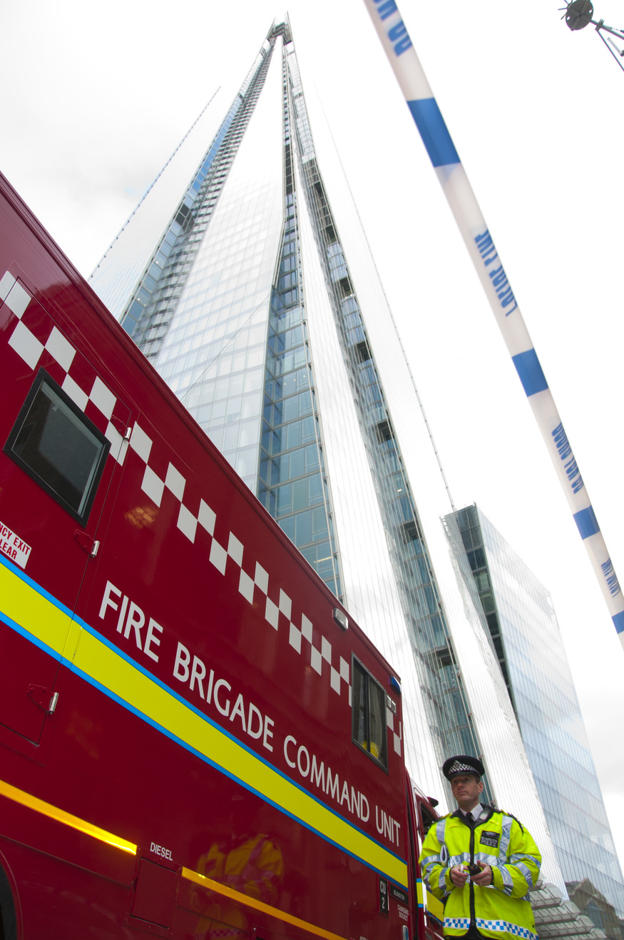 A police officer walks beside London Fire Brigade's Command Unit