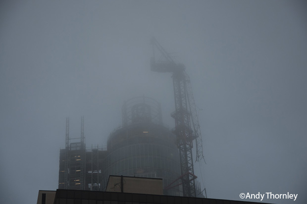 Low cloud obscures the crane which the helicopter crashed in, however it is still visible dangling from the tower in Vauxhall