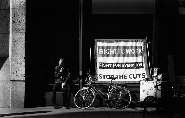 Right To Work : A passer-by sits down during the Atos protest. The Department for Work and Pensions. 31/8/2012