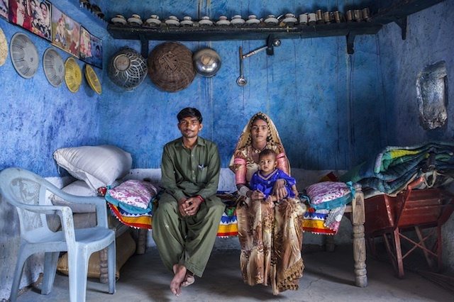 From left to right: Marjee, and Shugna, holding their daughter Kawila, sit in their house in District Umerkot, Sindh province, Pakistan, April 10, 2013.