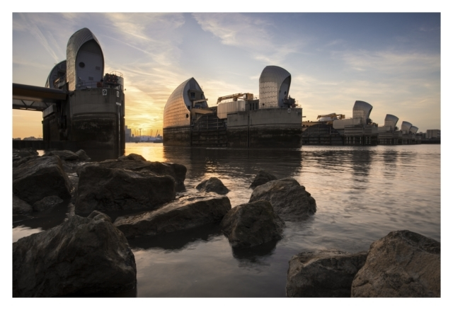 Protection.. The Thames Barrier at sunset as seen from the foreshore looking back towards the O2 Arena