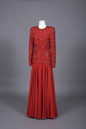 This evening gown by London-based designer Bruce Oldfield is fashionable with its wide shoulders and dropped waist while being modest with long sleeves, a high neckline and full-length skirt making it appropriate for Saudi Arabia, where it was first worn by Princess Diana in 1986. © Linda Sarna and Roberta Hurtig / Historic Royal Palaces / NTI Newsteam