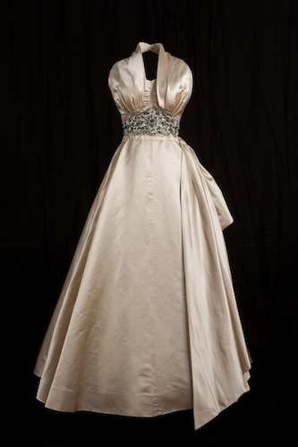 Worn by Princess Margaret at a film premier in London in 1951. This glamorous party frock, (plunging halter-neck design) marked a departure from the demure style traditionally adopted by Royal women. More Hollywood glamour than Royal wardrobe, its risque nature was widely reported by the press who were even more excited to find the Princess smoking a cigarette while wearing it. Historic Royal Palaces © Lord Linley and Lady Sarah Chatto.