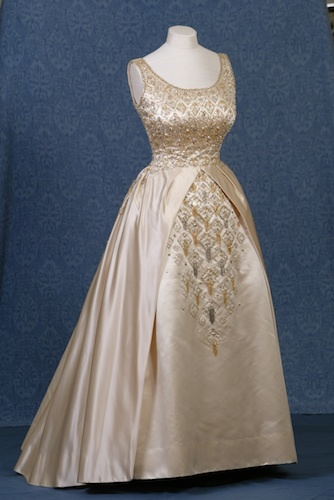 Worn by The Queen for the opening of the New Zealand parliament in 1963. Norman Hartnell was renowned for his intricately detailed beading. This gown of oyster-coloured duchesse satin is embroidered with pearls, beads, diamante and sequins. The scissor cut skirt creates fullness, revealing further embroidery underneath. Royal Collection Trust © Her Majesty Queen Elizabeth II 2013