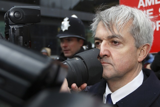 UNITED KINGDOM, London : Former British energy minister Chris Huhne (R) comes into contact with a photographers lens as he arrives at Southwark Crown Court in London, on March 11, 2013. Huhne and his ex-wife Vicky Pryce are due to be sentenced later Monday for perverting the course of justice over speeding points a decade ago. AFP PHOTO / JUSTIN TALLIS