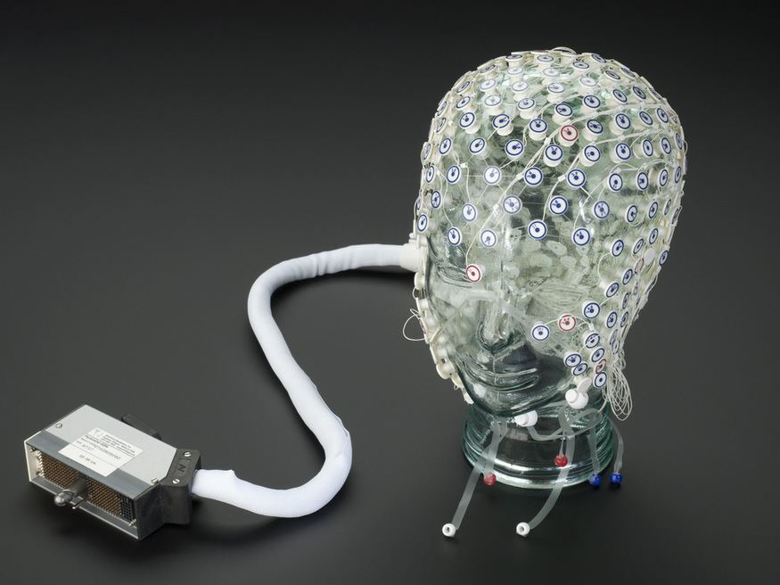 Geodesic EEG sensor net with head mount.  Front 3/4 view of whole object against graduated grey background.