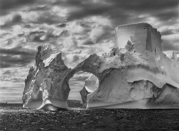 05-1-450/43  Iceberg between Paulet Island and the South Shetland Islands on the Antarctic Channel.  At sea level, earlier flotation levels are clearly visible where the ice has been polished by the ocean's constant movement. High above, a shape resembling a castle tower has been carved by wind erosion and detached pieces of ice.  The Antarctic Peninsula. January and February 2005.