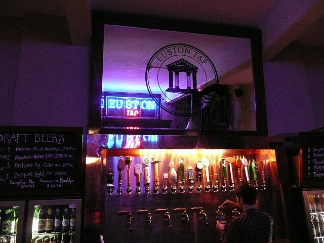 The Euston Tap's neon sign reflected in the mirror above the mighty range of taps.
