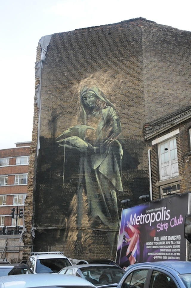 Faith 47 (South Africa): this is the tallest piece we've organised at around 4-5 floors high. Despite the size, Faith painted this piece in just one weekend using a cherry picker. The Madonna figure is holding a swan in her arms. If you're lucky enough to catch the piece when it's in direct sunlight it practically glows. Faith used gold spray paint around the piece and the effect is amazing. The effect of the changing ambient light is something you would rarely see in a gallery. Leonard Street opposite the Book Club – still there.