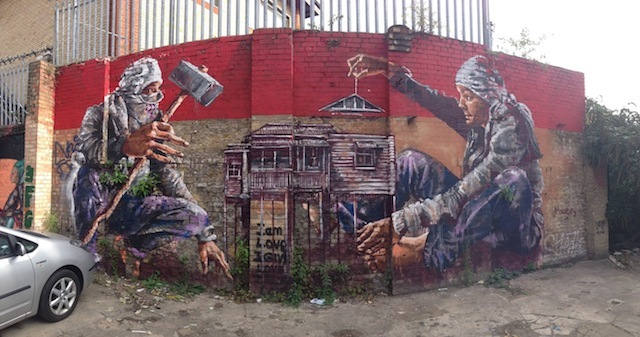 Fintan Magee (Australia): after the first couple of hundred walls, Londonist kindly asked its readers if they'd give us more walls. A lady from a co-working space in Dalston ended up giving us a bunch of walls in their car park. This piece, by Australian artist Fintan Magee, was the largest of around 10 murals we painted there. It depicts one man adding the roof onto an Australian Queenslander house while a second man with a hammer sits on the other side. Bootstrap Company car park near Abbott Street, Dalston – still there.