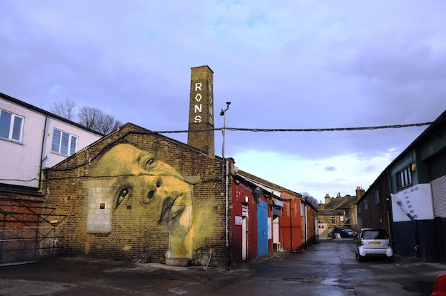 Jorge Rodriguez-Gerada (Cuba/USA): this piece is only a few weeks old. Jorge had a long weekend in London and only one free day to paint. We had only a days' notice but we called a friend Tim and he gave us a wall! Another friend Mark ferried Jorge around London to get paint and materials. We arrived on site at 10am and Jorge changed his plan – he was going to paint his daughter but he decided to paint one of the local children playing in the car park instead. We took photos of Okiki for the mural and after a little photoshopping, the mock-up was ready to go. Jorge started painting at midday and carried on through until 11 that night. One of the ladies who came to see the mural was so moved she choked back her emotions. Bussey Building, 133 Rye Lane, Peckham – still there.