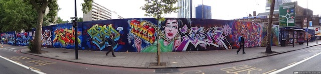 Paintstock: Elephant and Castle has a local arts festival, Elefest, each year. One of the festival's organisers, Rob Swain, went to great lengths to get approval for a 65m stretch of a building site hoarding. In the end we had 24 hours between the final go-ahead and painting the boards. The artists who painted included London graffiti legends Tizer and Noir, gonzo-stencilists Id-iom and 616, who is a weirdo! Thank you to property-developers Delancey for supporting with materials. New Kent Road, near Elephant and Castle Ral Station – still there.