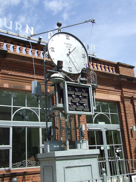 "This clock has stood outside London Zoo's Blackburn Pavilion tropical bird house since 2008. Designed by Tim Hunkin (who is known for creating unusual and dramatic clocks), the original brief was not for a clock, but rather just a monument showcasing the Victorian attitude to the animal world. The first plan was to design a clock in a cage, but the zoo rejected this idea as they were trying to do away with cages at the time. Every half hour, the people come to life, the two birds hanging from the wire begin to circle the clock, and the eight birds in front of the clock disappear one by one, to reappear around the edges of the clock face or on the ""Blackburn Pavilion"" lettering behind."