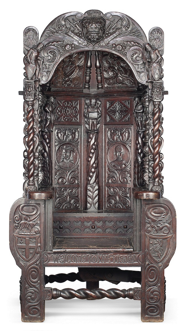 A highly unusual oak 'capture' chair of Elizabethan style, circa 1900. Its carvings include green man masks, portrait medallions and foliage. The arched canopy has a central boss carved with a Tudor Rose beneath a crown, dated 1603. It is engraved with 'Welcome to my friends' carved beneath. When the seat is sat on the 'capture' mechanism is released and a pair of iron bars trap the 'victim' in the chair. There is a concealed release mechanism to rear at base. (Estimate £25,000-£35,000)