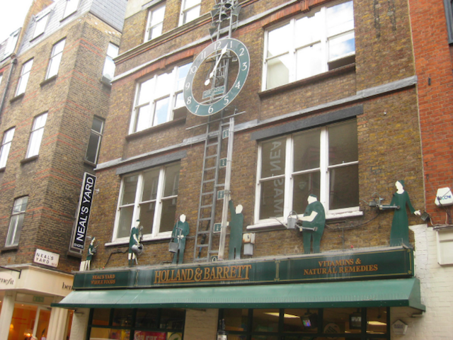 "Covent Garden's oft-overlooked Water Clock (or ""aquatic horology"" if you go by the adjacent plaque) was created in 1981 by Tim Hunkin (also responsible for the Blackburn Pavilion clock) and Andy Plant. The minutes are represented by the hollow tube, which slowly fills with water. Each hour, water tips from the roof into the cups above the clock face, setting off bells. The figurine people water window boxes (concealed behind the shop sign), causing plastic flowers to ""grow"". We can only assume that this is a homage to the floral history of the Covent Garden area. Sadly, the hands of the clock are no longer working and it is stuck in the position shown above."