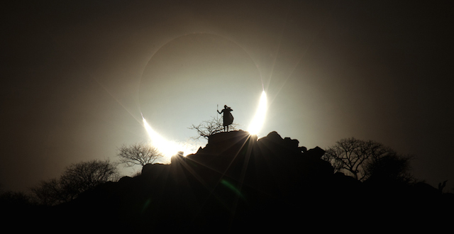 Sun and Moon sink together behind a Kenyan savannah skyline, locked in an eclipse in which the Moon is silhouetted against the Sun's bright disc. This rare example of a hybride solar eclipse took place in November 2013, beginning at sunrise over the western Atlantic as an annular eclipse, in which the Moon does not entirely block the Sun, leaving a bright ring uncovred. As the Moon's shadow swept across the ocean the eclipse became total, with the entirety of the Sun concealed from view. By the time the eclipse reached Kenya the Sun was once again emerging from behind the Moon, creating the breath-taking crescent shape at sunset. The photograph also acts as Kamenew's tribute to scheduled tour guide and photographic model for this shot, who was sadly Killed before he arrived in Kenya.