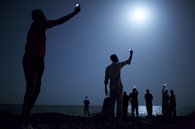 Impoverished African migrants crowd the night shore of Djibouti city, trying to capture inexpensive cell signals from neighboring Somalia—a tenuous link to relatives abroad. For more than 60,000 years our species has been relying on such intimate social connections to spread across the Earth.