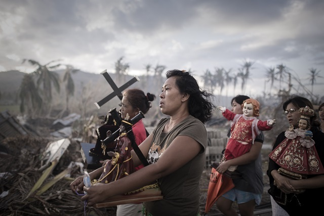 Survivors of typhoon Haiyan march during a religious procession in Tolosa, on the eastern island of Leyte. One of the strongest cyclones ever recorded, Haiyan left 8,000 people dead and missing and more than four million homeless after it hit the central Philippines. Photo: Philippe Lopez, France