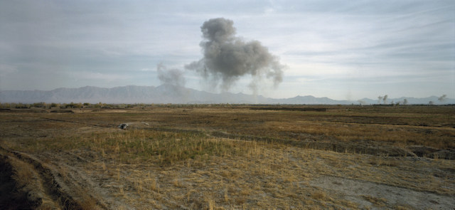 A puff of a smoke indicates the US bombing of a Taliban position. Otherwise there is no sign of any impact, highlighting how war has become more remote. Courtesy Luc Delahaye & Galerie Nathalie Obadia.