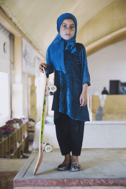 Skate Girl. Skate parks have been set up for girls in Afghanistan and the traditional dress contrasts with the brightly coloured skateboard. Copyright: Jessica Fulford-Dobson