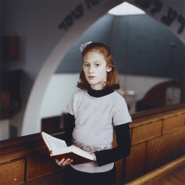 Chayla at Shul. Each year's prize doesn't feel complete without the obligatory shot of a red haired girl, and this year's has a great alignment between her hair colour and the benches. Copyright: Laura Pannack