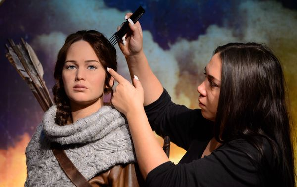 Gemma Sim makes final adjustments to Madame Tussauds newest figure, Katniss Everdeen, protagonist of the worldwide phenomenon The Hunger Games franchise, in its own immersive backdrop.     Following the release of The Hunger Games: Mockingjay - Part 1, Madame Tussauds has also launched wax likenesses of Katniss, portrayed by Academy Award® winner Jennifer Lawrence, at its New York and Hollywood attractions.  London's figure portrays Katniss' in her hunting outfit, which she wears in the second installment of the franchise, The Hunger Games: Catching Fire. Teamed with her iconic brown leather hunting jacket, are dark charcoal trousers, knee-length tie-up leather brown boots, plus brown leather quiver (arrow bag) and trademark bow. Her hair is also styled in her iconic braid.