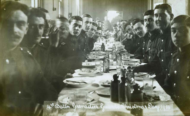 4th Battalion Grenadier Guards look to the camera during their Christmas meal at Chelsea Barracks, 1914.