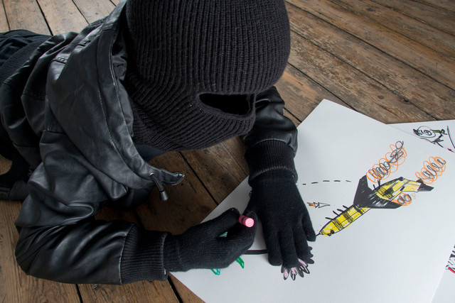 This child thug takes a break to do some drawing . Copyright Mark Jenkins.