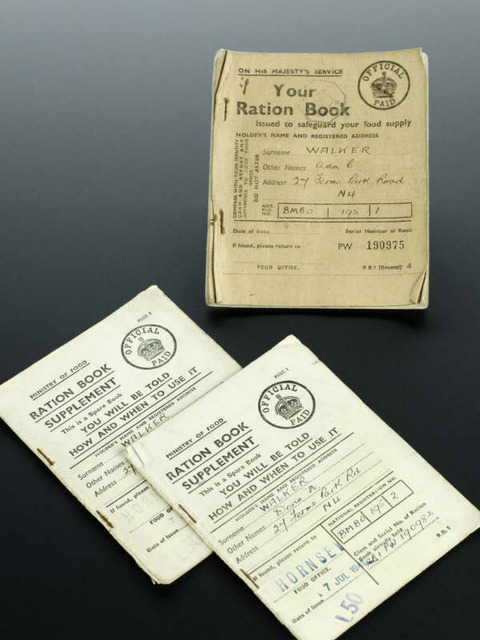Used Ration Book, and two partly used Ration Book Supplements, issued by the Ministry of Food during the second World War, to allow the limited purchasing of Meat, Bacon, Cooking Fats, Butter & Margarine and Sugar, all issued from Hornsey, North London, England, on July 7th 1941. Graduated black background.