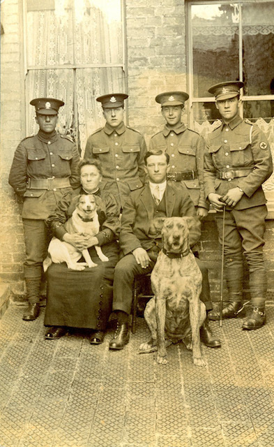 Four soldiers standing behind seated civilians and two dogs, 1st August 1915.