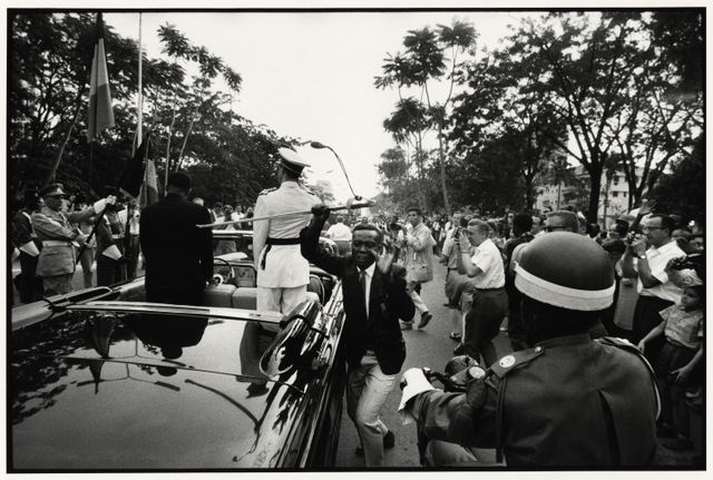 An image capturing the moment King Baudouin of Belgium's sword is stolen from his car as he arrives with the president of Congo. Robert Lebeck, 1960.
