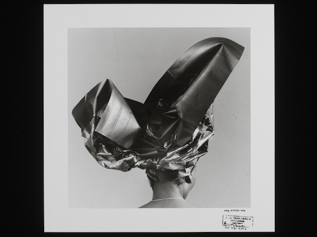 E.227-2013  Photograph Untitled, HG 423-04, 2004; A black and white photograph of an African woman seen from the back wearing an elaborate headtie, by J. D. 'Okhai Ojeikere, from the series 'Headties.' J.D. Okhai Ojeikere (1930-) 1970s