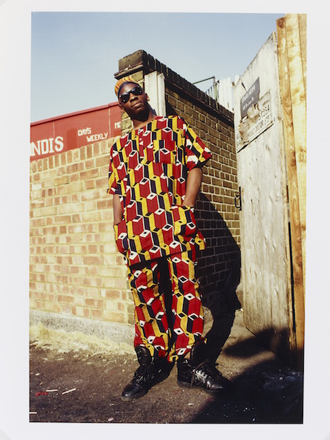 E.110-2012  Photograph African Homeboy-Brixton, London, 1987; Portrait photograph of a young man standing by a wall wearing colourful African influenced clothes and dark sunglasses. Normski ;  Brixton 1987 Fujifilm C-type colour print