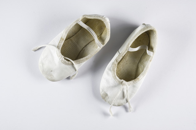 """""""My daughter, Grace, now 22, wore these when she was 4 as flower girl at the church wedding of friends.  I come across these every so often and think I should get rid of them, but never do.  They remind me of how that day I saw her with deepened understanding.  She found it very uncomfortable to stand for any length of time so she unobtrusively looked around, found a suitable spot, and sank to the floor to watch proceedings from there.  Such a little gesture that told of her clarity of judgment and mature good sense.  So I keep the shoes.""""  (Jane Petkovic)"""