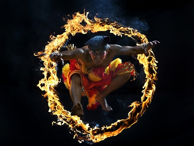 A man jumps through a ring of fire as part of an Indonesian cultural ritual. Copyright Aprison Aprison.
