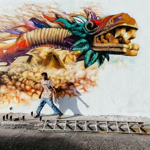 An artist paints a mural of Quetzalcoatl, the Aztec sky god. Copyright Hector Munoz Huerta.