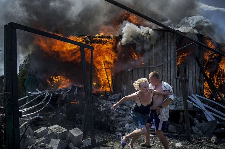 Two people flee a burning house in Ukraine. Copyright Valery Melnikov.