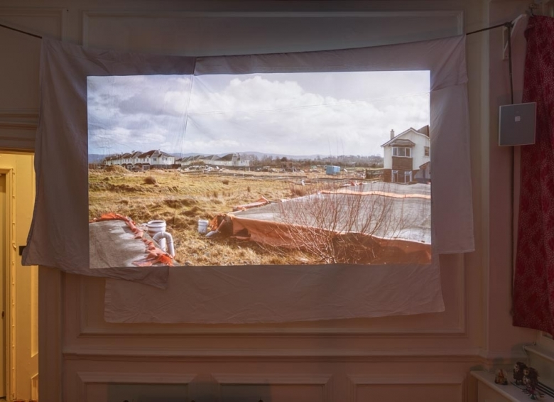 Abandoned developments in Ireland are projected onto a sheet hanging from the wall. © Copyright 2015 Frith Street Gallery