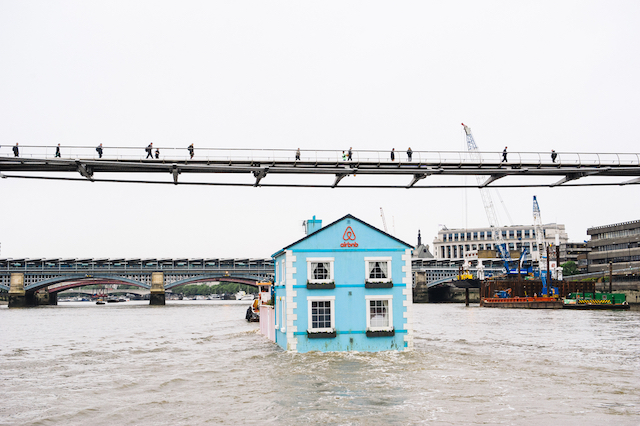 Monday 18th May 2015, London:  Airbnb's latest London listing is pictured floating down the River Thames this morning.  This pic: The house going under the Millennium Bridge  The fully functioning Floating House will sail down the Thames to celebrate new rules that mean that Londoners – like the rest of the UK – can earn a 15 per cent pay rise* by sharing their homes through sites like Airbnb. Passing under Tower Bridge before gliding past the Shard on its maiden voyage, the House will meander along the river throughout the week until Saturday 22 May.  Copyright: © Mikael Buck / Airbnb +44 (0) 782 820 1042 http://www.mikaelbuck.com