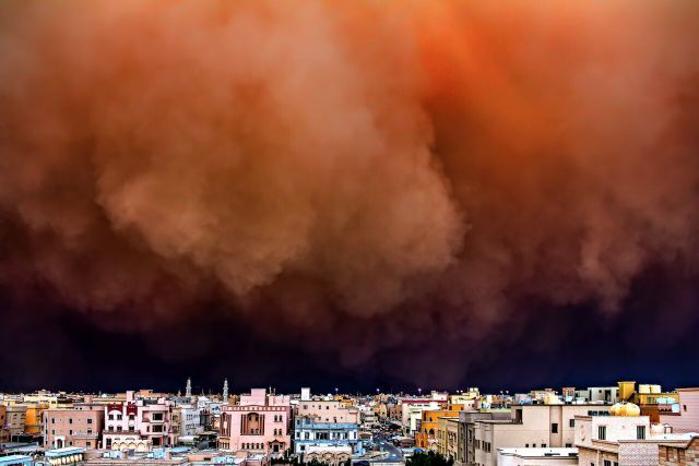 Houses are dwarfed as a dust storm rolls into Kuwait city. Copyright Rizalde Cayanan
